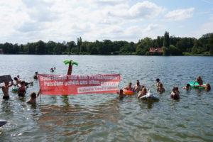 """Menschen beim Baden mit einem Banner mit der Aufschrift: """"Badestellen sind kein Privateigentum! Potsdam gehört uns allen."""""""